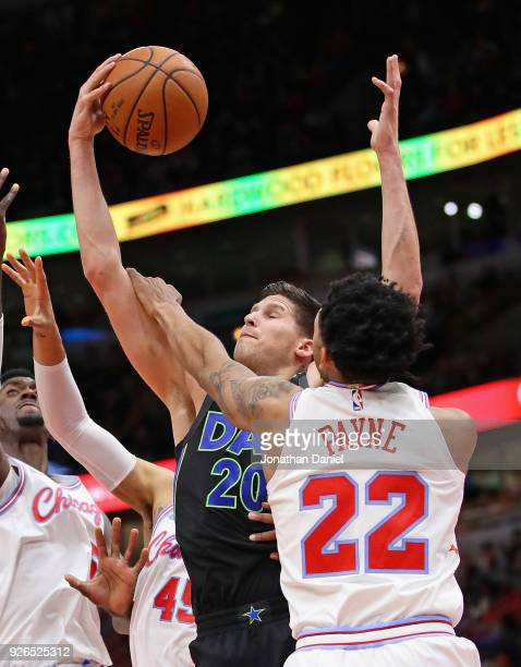 Doug McDermott of the Dallas Mavericks is fouled by Cameron Payne of the Chicago Bulls at the United Center on March 2 2018 in Chicago Illinois NOTE...