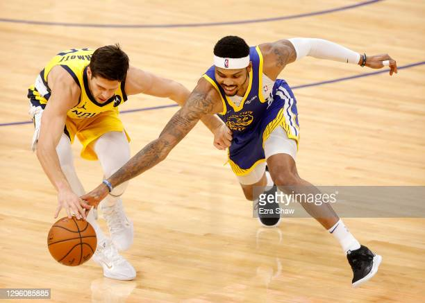 Doug McDermott of the Indiana Pacers and Kent Bazemore of the Golden State Warriors go for a loose ball at Chase Center on January 12, 2021 in San...