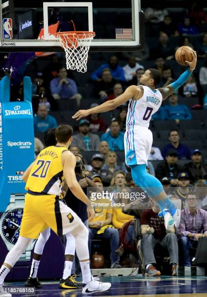 Doug McDermott of the Indiana Pacers watches as Miles Bridges of the Charlotte Hornets dunks the ball during their game at Spectrum Center on...