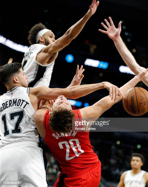Doug McDermott of the San Antonio Spurs and Derrick White block shot of Alperen Sengun of the Houston Rockets of a pre-season game at AT&T Center on...