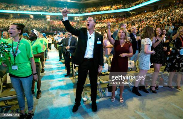 Doug McMillon Walmart CEO gives the Walmart cheer with wife Shelley during the annual shareholders meeting event on June 1 2018 in Fayetteville...
