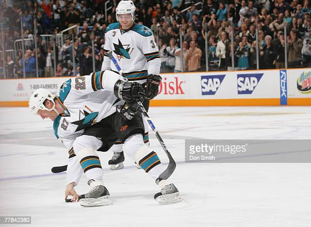 Doug Murray of the San Jose Sharks watches Jeremy Roenick of the San Jose Sharks pick up the puck after his 500th career goal during an NHL game...