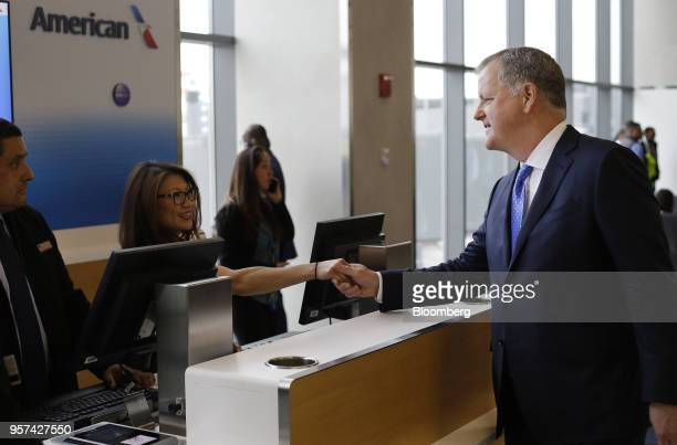 Doug Parker chairman and chief executive officer of American Airlines Group Inc shakes hands with an employee during an event to mark the opening of...