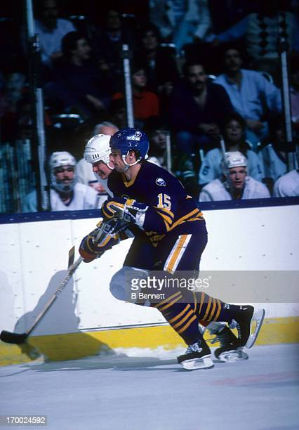 Doug Smith of the Buffalo Sabres and Mikko Makela of the New York Islanders skate for the puck on April 4 1987 at the Nassau Coliseum in Uniondale...