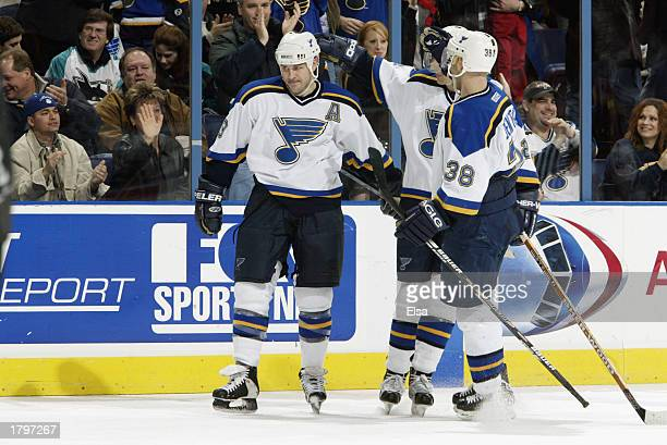Doug Weight of the St Louis Blues is congratulated by teammates Al MacInnis and Pavol Demitra after Weight scored an unassisted goal against the San...