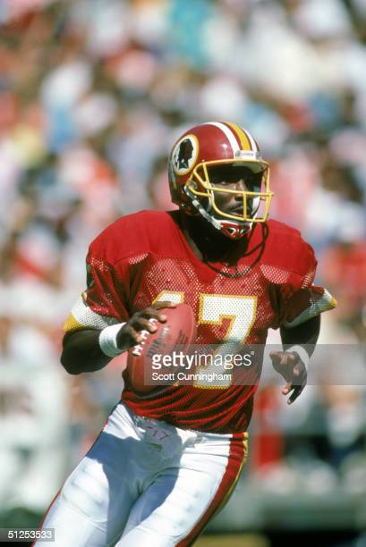 Doug Williams of the Washington Redskins moves back to pass during a 1987 NFL season game