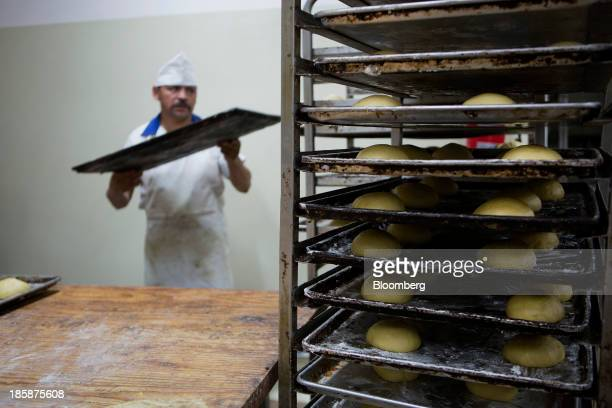 Dough for pan de muerto sits on racks before going in the oven at La Ideal bakery in Mexico City Mexico on Thursday Oct 24 2013 The pan de muerto or...