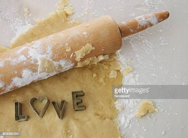 Dough, rolling pin and pastry cutters spelling word love