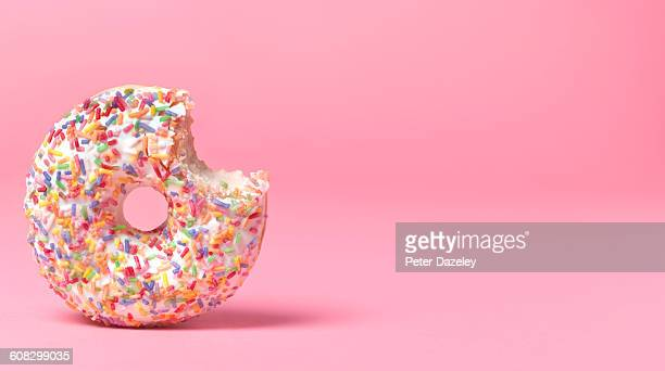 doughnut on pink with bite out - donut stock pictures, royalty-free photos & images