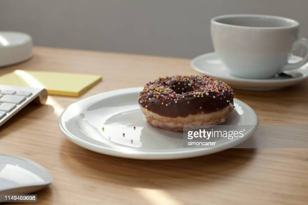 Doughnut on plate. Home office interior.