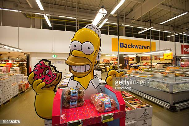 A doughnut promotion stand featuring cartoon character Homer Simpson stands inside a Metro AG Cash Carry wholesale store in Duesseldorf Germany on...