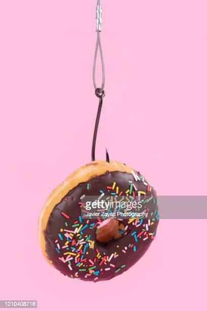doughnut skewered on a hook - angelhaken stock-fotos und bilder