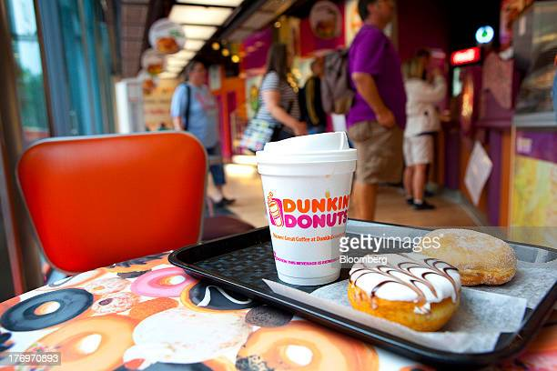 Doughnuts and a beverage cup are seen on a tray as customers wait to be served at a sales counter in this arranged photograph taken inside a Dunkin'...