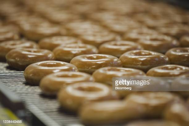 Doughnuts on a production line inside a Krispy Kreme Doughnuts Inc. Store in the Times Square neighborhood of New York, U.S., on Thursday, Sept. 10,...