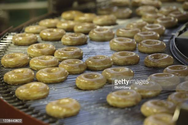 Doughnuts on an production line inside a Krispy Kreme Doughnuts Inc. Store in the Times Square neighborhood of New York, U.S., on Thursday, Sept. 10,...