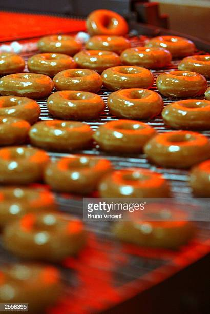 Doughnuts roll off the production line at the opening of the first Krispy Kreme shop in Harrods department store October 3 2003 in London