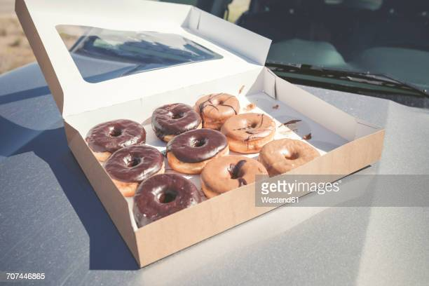 Doughnuts with different icings in a box on car bonnet