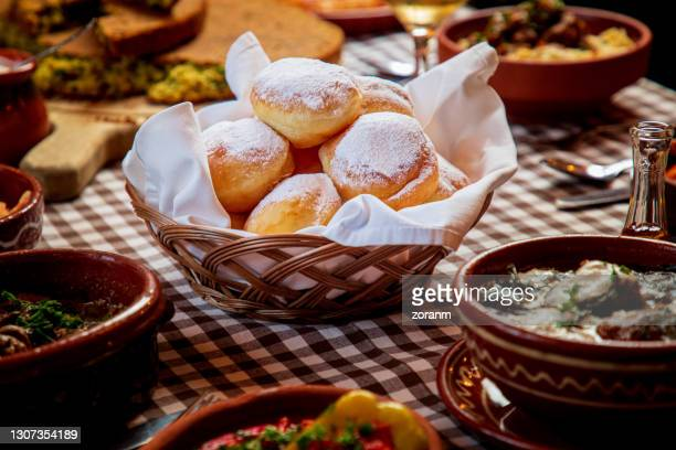 doughnuts with powdered sugar on top in wicker basket on traditional food buffet - sufganiyah stock pictures, royalty-free photos & images