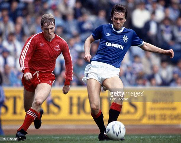 Dougie Bell of Glasgow Rangers passes the ball with Aberdeen's Stuart McKimmie moving in during the match at Ibrox Stadium in Glasgow 28th September...