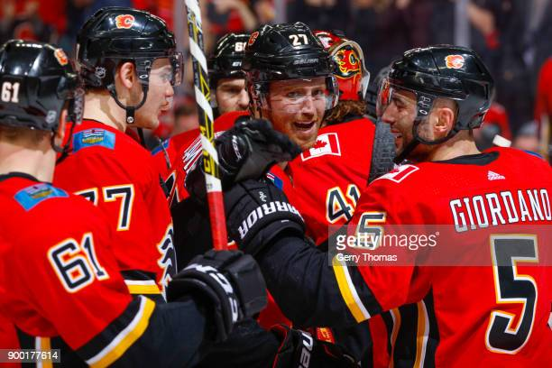 Dougie Hamilton Mark Giordano and teammates of the Calgary Flames celebrate in an NHL game on December 31 2017 at the Scotiabank Saddledome in...