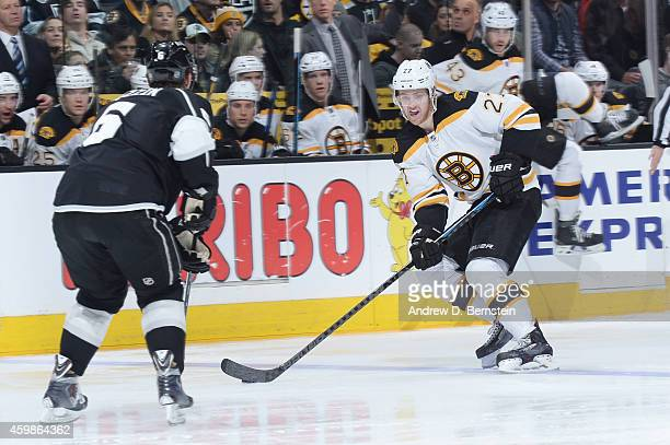Dougie Hamilton of the Boston Bruins handles the puck against Jake Muzzin of the Los Angeles Kings at STAPLES Center on December 02 2014 in Los...