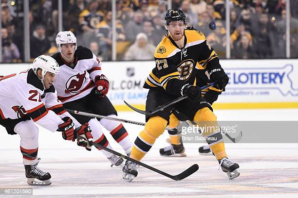 Dougie Hamilton of the Boston Bruins keeps his eye on the loose puck against Scott Gomez of the New Jersey Devils at the TD Garden on January 8 2015...
