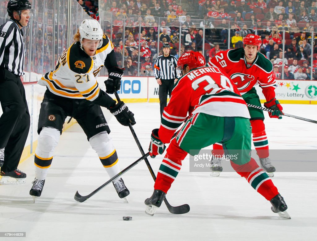 Dougie Hamilton #27 of the Boston Bruins plays the puck against Jon Merrill #34 of the New Jersey Devils during the game at the Prudential Center on March 18, 2014 in Newark, New Jersey.