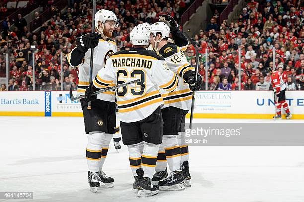 Dougie Hamilton of the Boston Bruins skate in to celebrate with teammates after scoring against the Chicago Blackhawks in the second period during...