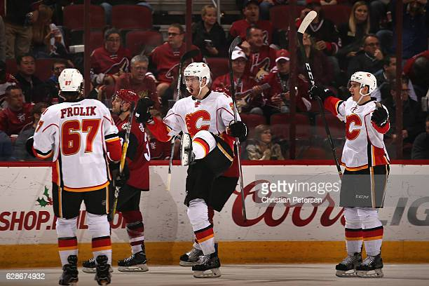 Dougie Hamilton of the Calgary Flames celebrates his game winning goal with Michael Frolik and Mikael Backlund against the Arizona Coyotes in...