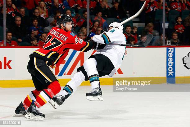 Dougie Hamilton of the Calgary Flames checks Joe Pavelski of the San Jose Sharks during an NHL game on January 11 2017 at the Scotiabank Saddledome...