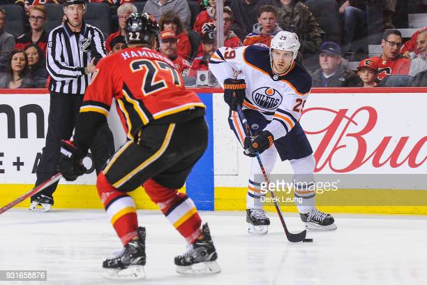 Dougie Hamilton of the Calgary Flames defends against Leon Draisaitl of the Edmonton Oilers during an NHL game at Scotiabank Saddledome on March 13...