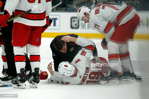 Dougie Hamilton of the Carolina Hurricanes is checked on by head athletic trainer Doug Bennett after getting injured during the second period against...