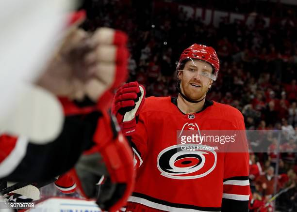 Dougie Hamilton of the Carolina Hurricanes skates back to the bench to celebrate with teammates after scoring a goal during an NHL game against the...