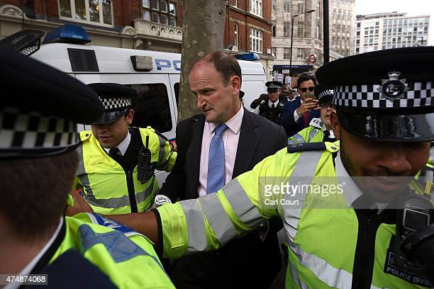 Douglas Carswell is helped away by police officers after being caught up in an antiausterity protest as they demonstrated on May 27 2015 in London...