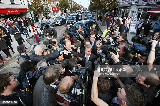 Douglas Carswell of the UK Independence Party and party leader Nigel Farage are surrounded by reporters on October 10 2014 in ClactononSea England Mr...
