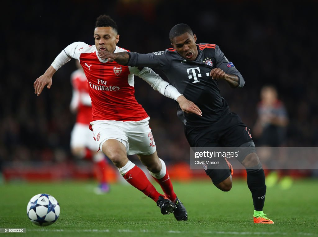 Douglas Costa of Bayern Muenchen and Francis Coquelin of Arsenal battle for the ball during the UEFA Champions League Round of 16 second leg match between Arsenal FC and FC Bayern Muenchen at Emirates Stadium on March 7, 2017 in London, United Kingdom.