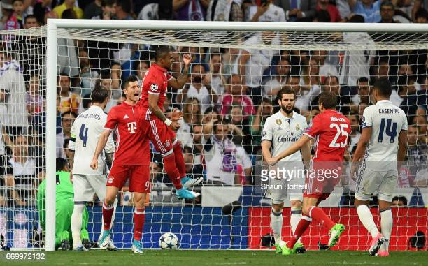 Douglas Costa of Bayern Muenchen celebrates after Sergio Ramos of Real Madrid scored a own goal for Bayern Muenchen's second goal during the UEFA...