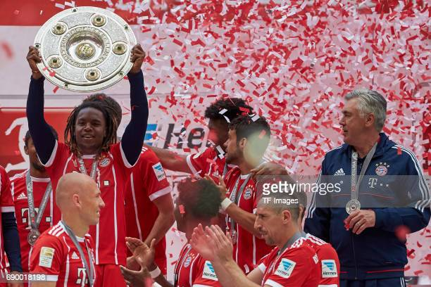 Douglas Costa of Bayern Muenchen poses with the Championship trophy in celebration of the 67th German Championship title following the Bundesliga...