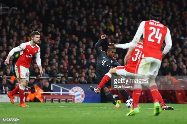 Douglas Costa of Bayern Muenchen scores their third goal during the UEFA Champions League Round of 16 second leg match between Arsenal FC and FC...