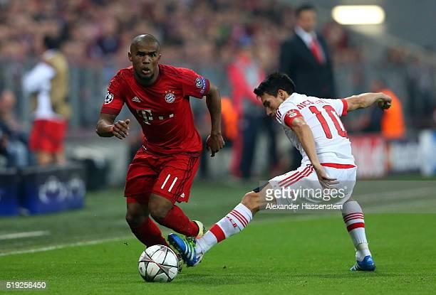 Douglas Costa of Bayern Munich evades Nicolas Gaitan of Benfica during the UEFA Champions League quarter final first leg match between FC Bayern...