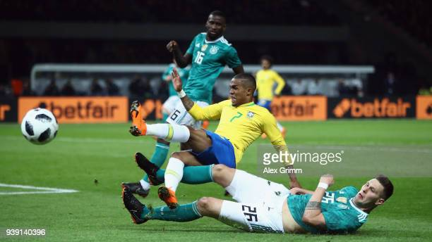 Douglas Costa of Brazil is challenged by Niklas Suele of Germany during the international friendly match between Germany and Brazil at Olympiastadion...