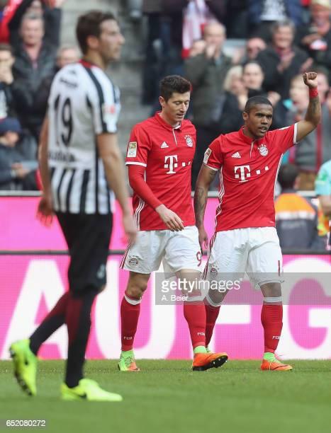 Douglas Costa of FC Bayern Muenchen celebrates his first goal with teammate Robert Lewandowski as David Abraham of Eintracht Frankfurt reacts during...