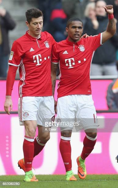 Douglas Costa of FC Bayern Muenchen celebrates his first goal with teammate Robert Lewandowski during the Bundesliga match between Bayern Muenchen...
