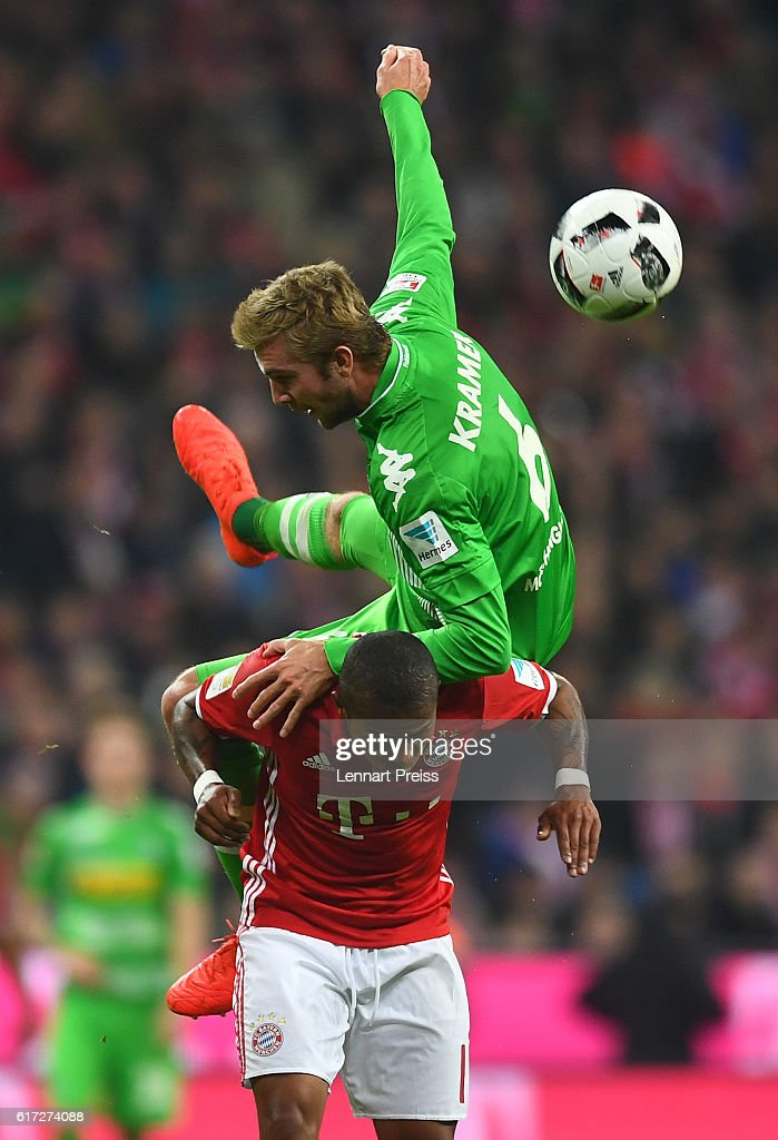 Douglas Costa of FC Bayern Muenchen challenges Christoph Kramer (top) of Borussia Moenchengladbach during the Bundesliga match between FC Bayern Muenchen and Borussia Moenchengladbach at Allianz Arena on October 22, 2016 in Munich, Germany.