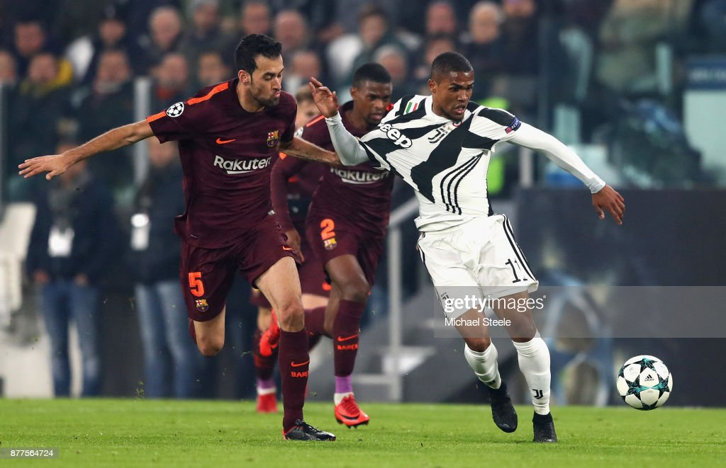 Douglas Costa of Juventus and Sergio Busquets of Barcelona battle for possession during the UEFA Champions League group D match between Juventus and FC Barcelona at Allianz Stadium on November 22, 2017 in Turin, Italy.
