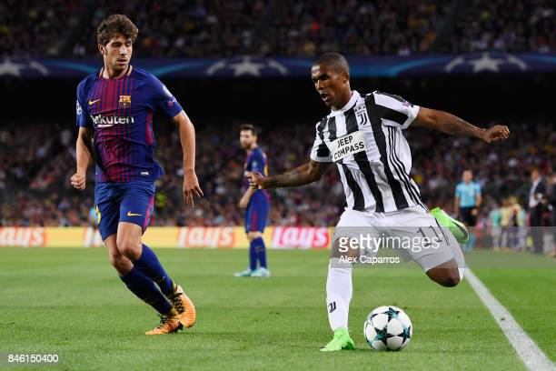 Douglas Costa of Juventus attempts to get past Andre Gomes of Barcelona during the UEFA Champions League Group D match between FC Barcelona and...