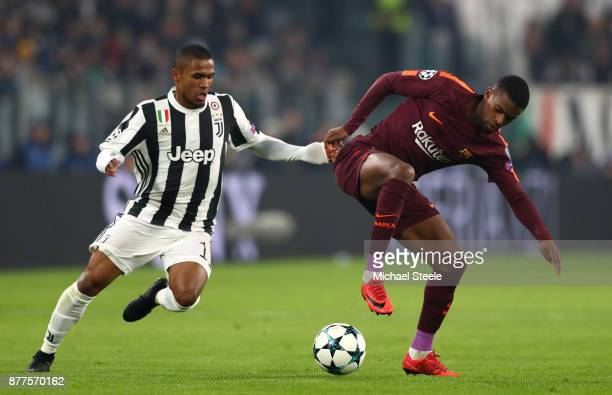 Douglas Costa of Juventus challenges Nelson Semedo of Barcelona during the UEFA Champions League group D match between Juventus and FC Barcelona at...