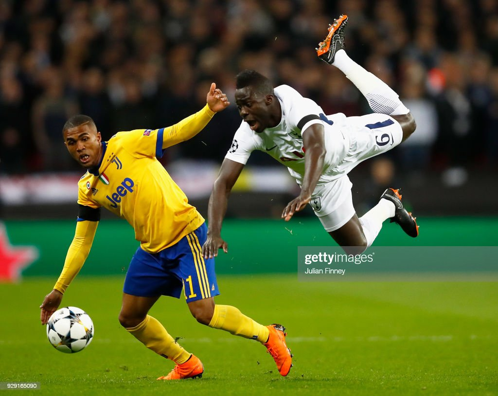 Douglas Costa of Juventus collides with Davinson Sanchez of Tottenham Hotspur during the UEFA Champions League Round of 16 Second Leg match between Tottenham Hotspur and Juventus at Wembley Stadium on March 7, 2018 in London, United Kingdom.