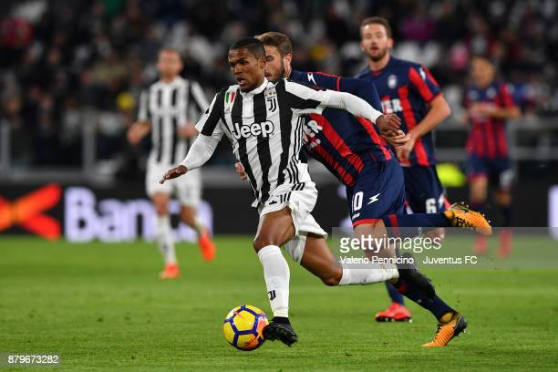 Douglas Costa of Juventus competes for the ball with Andrea Barberis of Crotone during the Serie A match between Juventus and FC Crotone at Allianz...