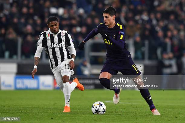 Douglas Costa of Juventus competes for the ball with Erik Lamela of Tottenham Hotspur FC during the UEFA Champions League Round of 16 First Leg match...